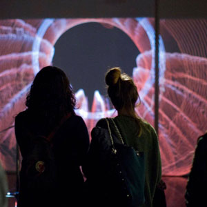 Two women look at a videoprojection that depicts the graphical visualization of an earthquake.