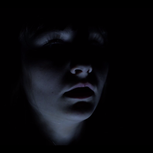 The face of a young woman in the dark.